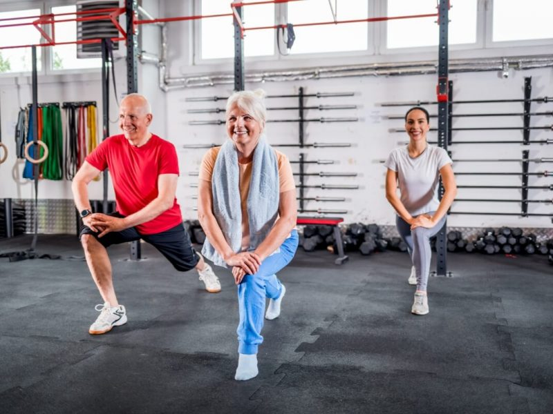 personal-trainer-with-senior-couple-doing-rehab-ex-UB93AER